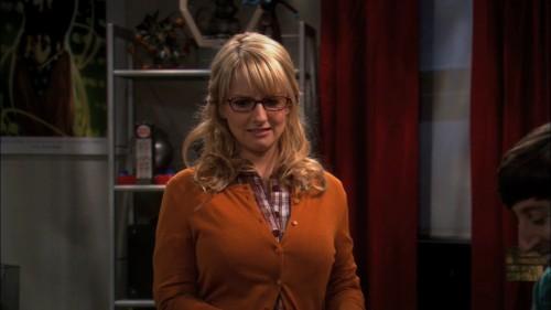 Bernadettes orange cardigan over a plaid shirt