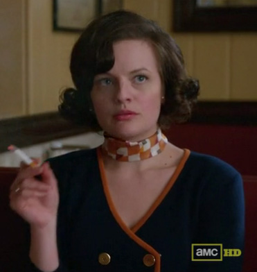Peggy's navy sweater with orange trim and orange scarf on Mad Men