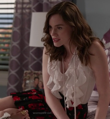 Charlotte's white ruffle top and black rose print skirt on Revenge