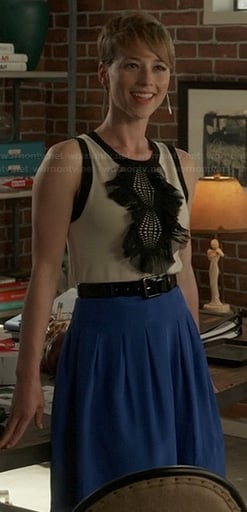 Margaux's black and white ruffle front top and blue pleated skirt on Revenge
