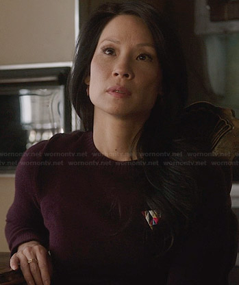 Joan's purple sweater dress with embroidered triangle detail on Elementary