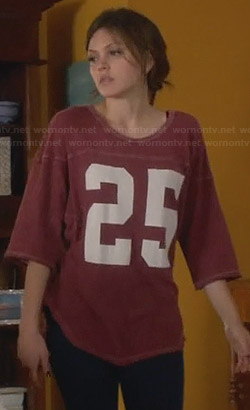 "Emery's red ""25"" tee on Star-Crossed"