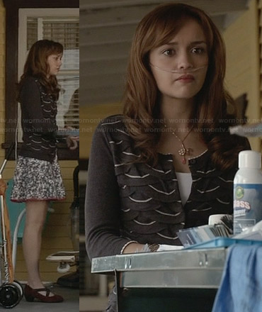 Emma's black cardigan with white scalloped pattern and floral skirt on Bates Motel