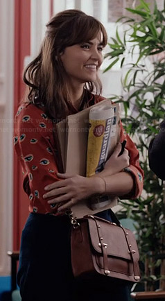 Clara's orange eye print shirt and tan bag on Doctor Who