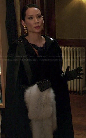Joan's long black hooded cape and fur stone on Elementary