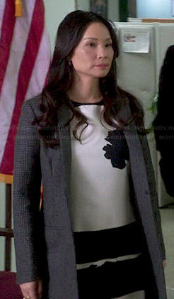 Joan's black and white flower and stripe dress and grey coat on Elementary