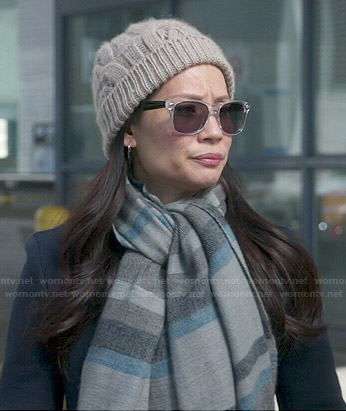 Joan's long navy coat and striped scarf on Elementary