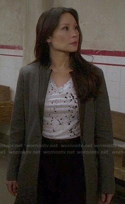Joan's grey coat and paint splatter tee on Elementary