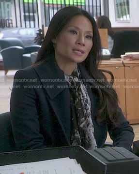 Joan's navy coat and black and white printed scarf on Elementary