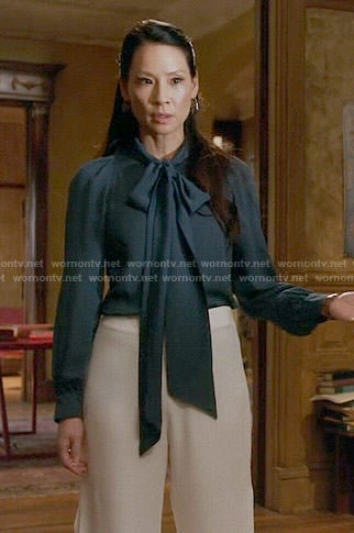 Joan's teal neck bow blouse and white wide leg pants on Elementary