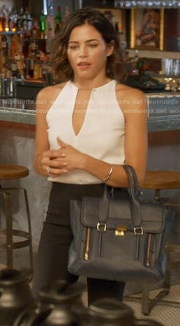 Lucy's white keyhole top and navy bag on Supergirl
