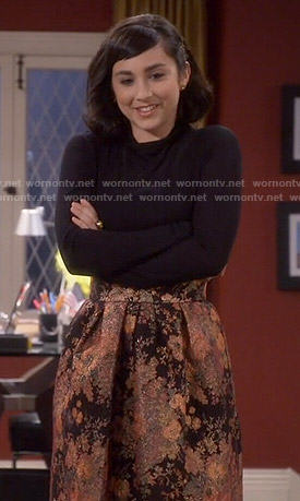 Mandy's orange floral skirt and black turtleneck on Last Man Standing