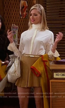 Caroline's high neck blouse and yellow pleated skirt on 2 Broke Girls