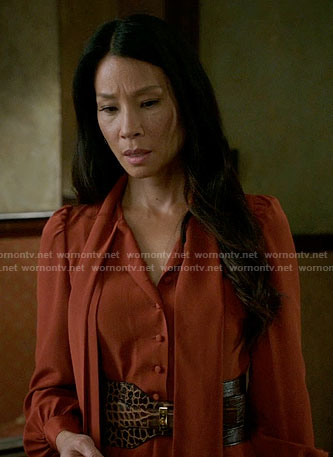 Joan's orange tie neck dress and wide croc belt on Elementary