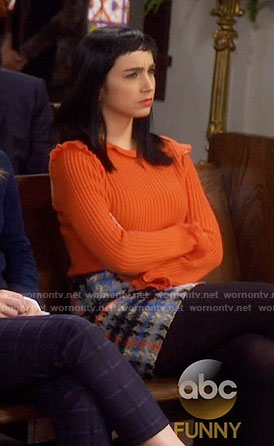 Mandy's orange ruffled sweater and plaid skirt on Last Man Standing