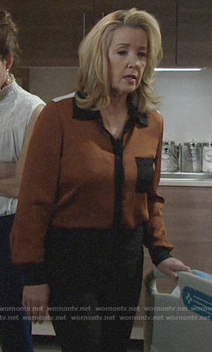 Nikki's orange blouse with black trim on The Young and the Restless