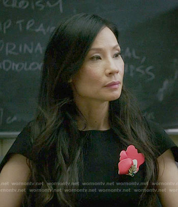 Joan's black dress with red brooch on Elementary