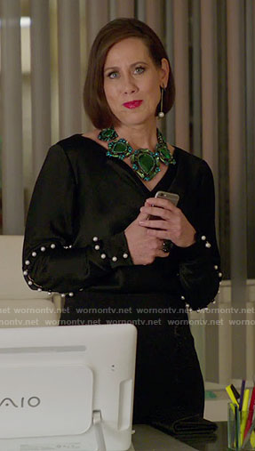 Diana's black pearl embellished top and green necklace on Younger