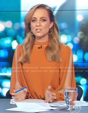 Carrie's orange long slit sleeve top on The Project