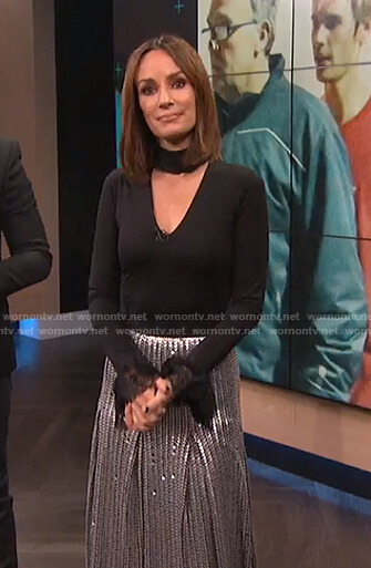 Catt's black choker neck top with lace cuffs and sequin pleated skirt on E! News