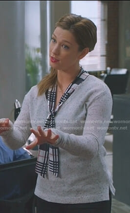 Katie's plaid tie neck top and grey v-neck sweater on Great News