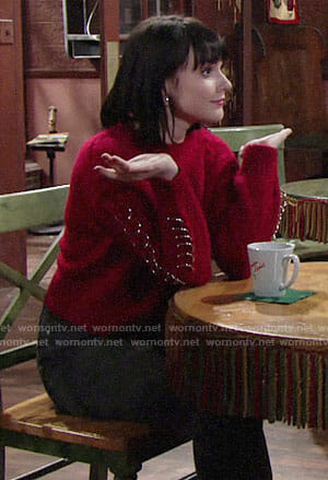 Tessa's red sweater with rings on The Young and the Restless