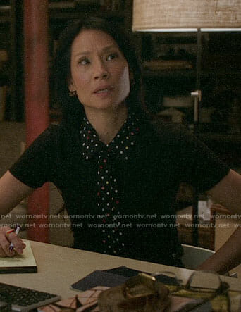 Joan's black top with polka dot collar and tie on Elementary