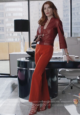 Kitty's red leather split neck top and orange pants on Dietland
