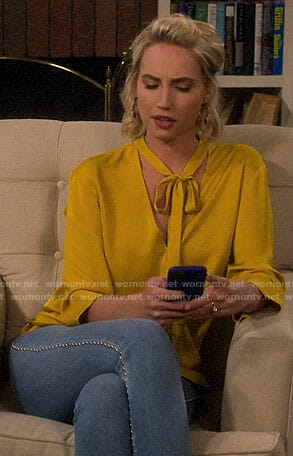 Mandy's yellow tie neck blouse and studded jeans on Last Man Standing