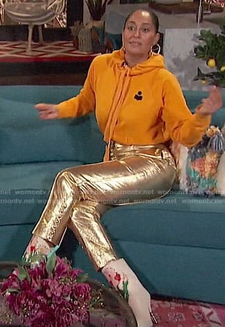 Tracee Ellis Ross's yellow hoodie, gold pants, and floral boots on Busy Tonight