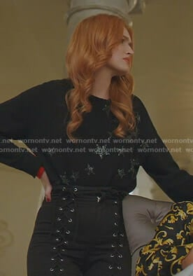 Kirby's black star print sweater and  lace-up pants on Dynasty