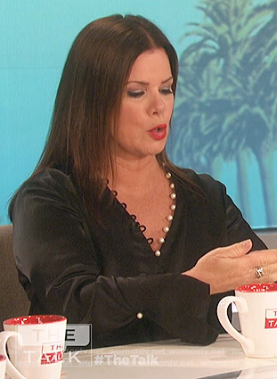 Marcia Gay Harden's black pearl trim wrap blouse on The Talk