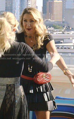 Kary's leather pleated mini skirt and red belt bag on The Real Housewives of Dallas