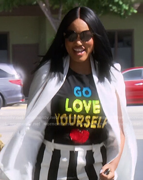 Garcelle's black Go Love Yourself tee and striped pants on The Real Housewives of Beverly Hills