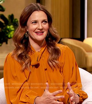 Drew's orange tie neck blouse on The Drew Barrymore Show