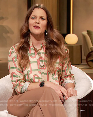 Drew's beige monogram print tie neck blouse on The Drew Barrymore Show