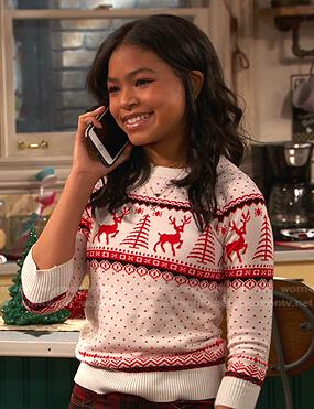 Nia's white reindeer print sweater on Ravens Home