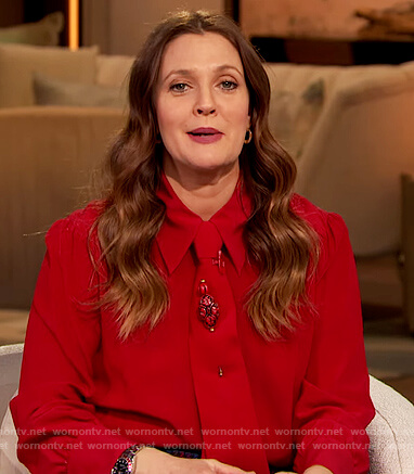 Drew's red tie neck blouse and plaid pants on The Drew Barrymore Show