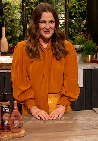 Drew's orange tie neck blouse and sequin skirt on The Drew Barrymore Show