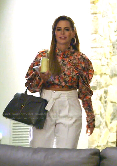 D'Andra's floral blouse and white belted pants on The Real Housewives of Dallas