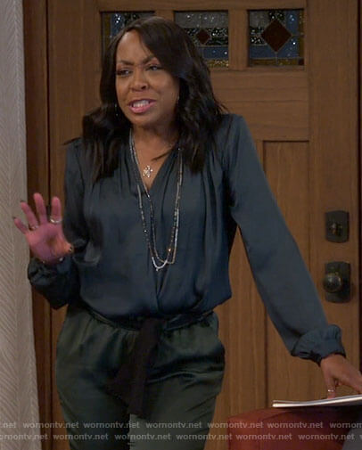 Tina's navy draped blouse on The Neighborhood