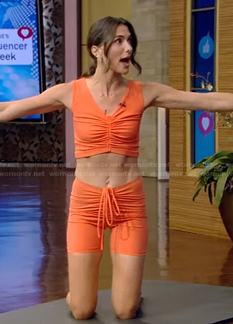 Melissa Wood-Tepperberg's orange ruched sport bra and biker shorts on Live with Kelly and Ryan