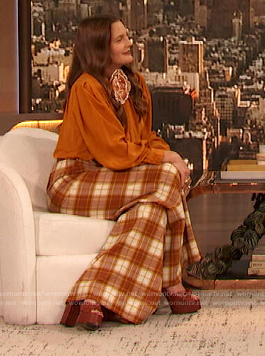 Drew's orange tie neck blouse and plaid pants on The Drew Barrymore Show